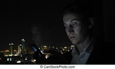 Young businessman in office suit is browsing smartphone near the window with city view.