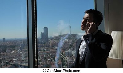 Young businessman in office suit is talking phone near the...