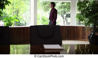 Worried young business man looks out of the office window at work