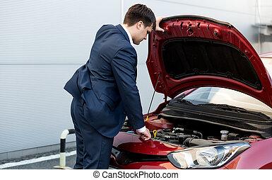 businessman in suit opening bonnet of open car