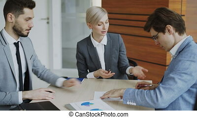 Young businessman in suit signing contract and shake hands with his colleague while corporate lawyer explaining details of partnership sitting in modern office