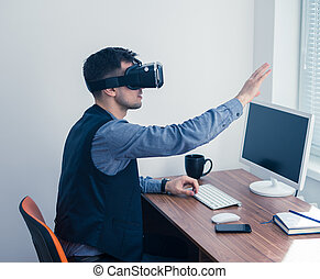 Young businessman in vr glasses drawing chart with gesture