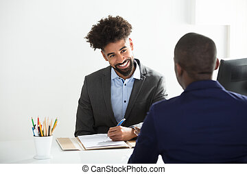 Businessman Interviewing Male Candidate - Young Businessman...