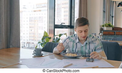 Young businessman is at business lunch, using phone sitting in cafe.
