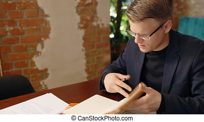 Young businessman is in working process with notebook at...