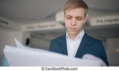 Young businessman is researching investment project standing...