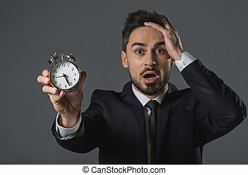 Young businessman is shocked about time