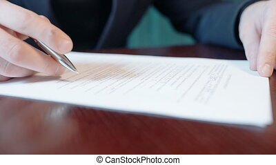 Young businessman is signing documents, sitting at table in...