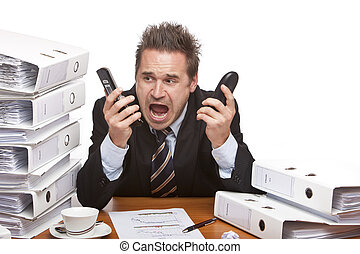 Young businessman is sitting on desk betweent folder stacks and screams into two telephones.  Isolated on white.