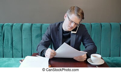 Young businessman is talking on phone, sitting at table in cafe.