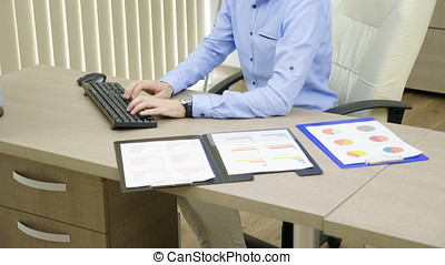Young businessman is working in his office at the computer next to folders filled with charts