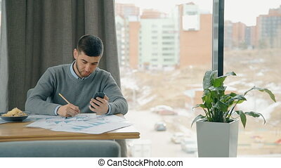 Young businessman is working on project, using smartphone at table in cafe.