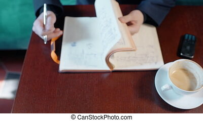 Young businessman is working with notebook, sitting at table in cafe interior.