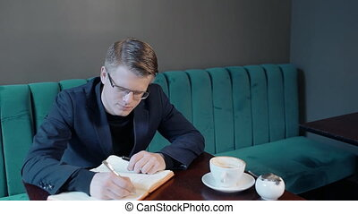 Young businessman is writing in notebook, uses phone,...