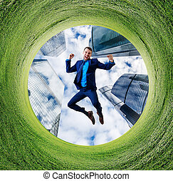 Young businessman jumps up into green field circle.