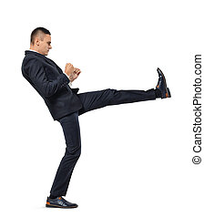 Young businessman kicking someone or something isolated on a white background