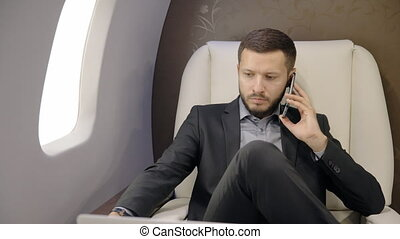 Young businessman lawyer talking on phone, using tablet in...