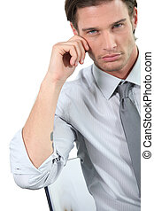 Young businessman leaning on his chair