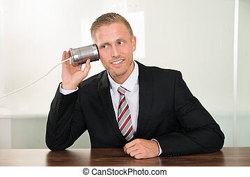 Businessman Listening From Tin Cans Phone