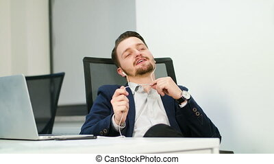 Young Businessman Listening to Music in Office