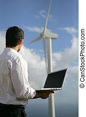 young businessman looking at a wind turbine