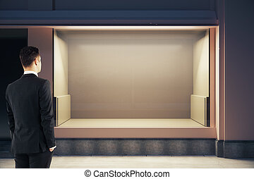 Young businessman looking at showcase