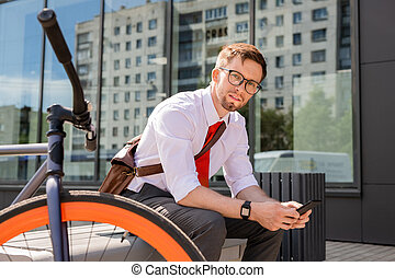Young businessman looking at you while sitting on bench and using smartphone