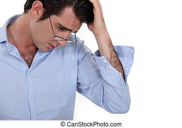 young businessman looking tired with glasses lowered and hand to his head