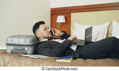 Young businessman lying on bed and suitcase talking phone and working with laptop from his hotel room. Travel, business and people concept