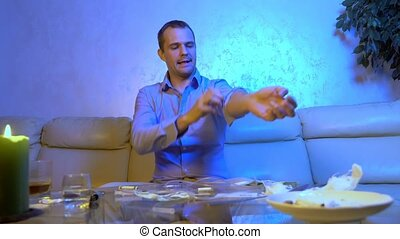 young businessman makes himself an injection of drugs while sitting on a sofa in the living room at a table with alcohol and drugs.
