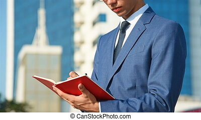 Young Businessman Makes Notes In Diary On Background Of Business Center