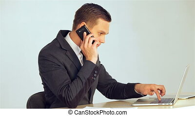 Young businessman making a call in response to the data...