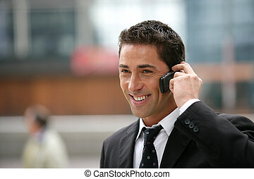 Young businessman making a call outside