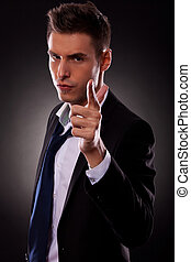 young businessman making a gun gesture
