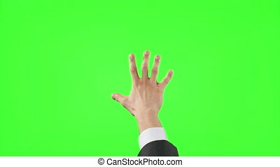 Young businessman making hand gestures on green screen