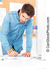 Young businessman making notes while standing at the office desk