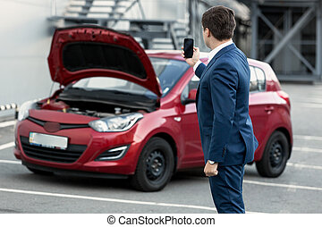 businessman making photo on phone of breakdown car for insurance