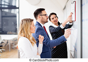 Young businessman making presentation and showing diagram on whiteboard