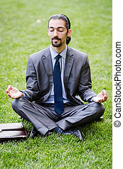 Young businessman meditating in the garden