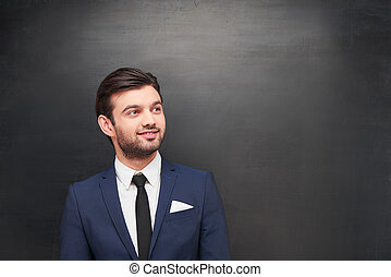 Young businessman on chalkboard background