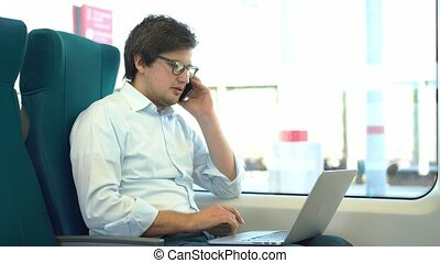 Young businessman on phone and using laptop in a train