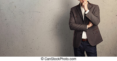Young businessman on the background of a concrete wall