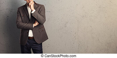 Young businessman on the background of a concrete wall.
