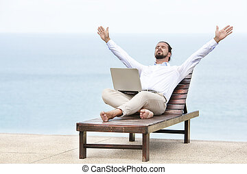6ba124f64b Young businessman relaxing on a deck chair using his tablet. Young ...