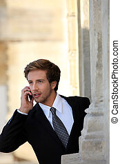 Young businessman on the phone by a stone building