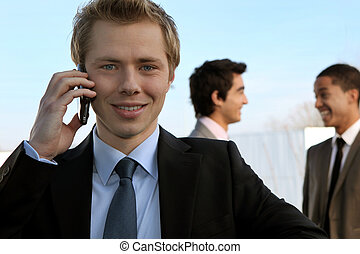 Young businessman on the phone in front of colleagues