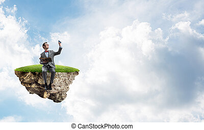 Young businessman or student floating in sky and studying the science