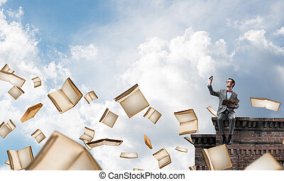 Young businessman or student studying the science and books flying around