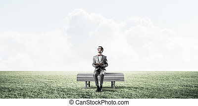 Young businessman or student studying the science in summer park