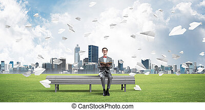 Young businessman or student studying the science and paper planes flying around